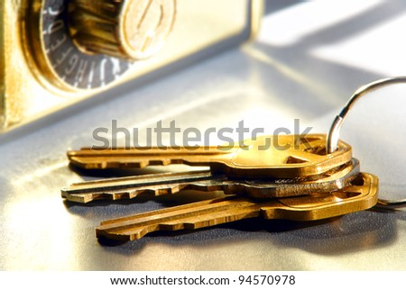 Set of house keys on a ring and real estate brokerage Realtor agent combination safety lock box on shiny reflective surface - stock photo