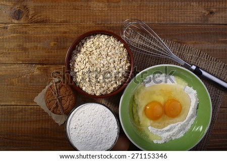 Set of ingredients and appliances for baking with yolk in flour and oatmeal on wooden table top copyspace, horizontal picture - stock photo