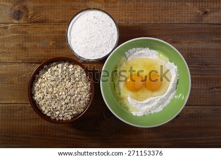 Set of ingredients for baking with yolk in flour oatmeal on wooden table top, horizontal picture - stock photo