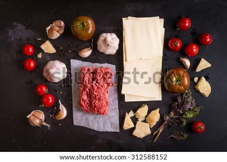 Set of ingredients for italian lasagna. Pasta, tomatoes, fresh ground meat, parmesan, mozzarella, basil, garlic on a rustic chalkboard. Overhead - stock photo