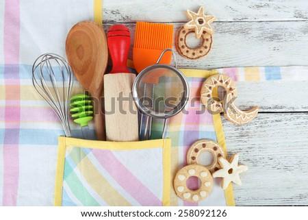 Set of kitchen utensils in pocket of apron, closeup - stock photo