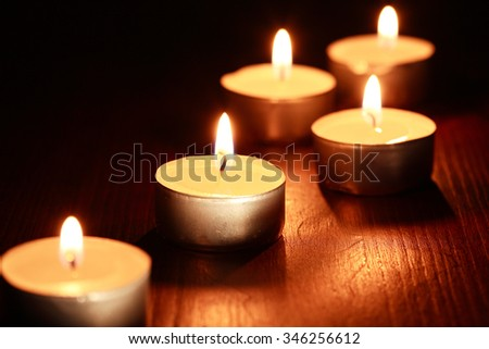 Set of lighting candles on wooden board against dark background