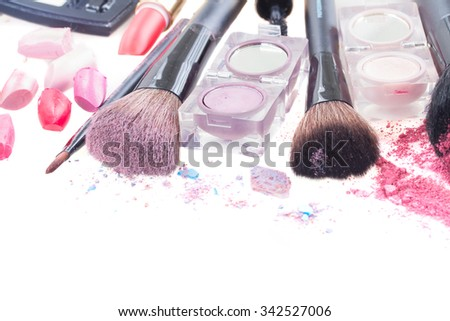 set of  make up brushes, lipsticks and  eye  shadows with crumbles  isolated on white background