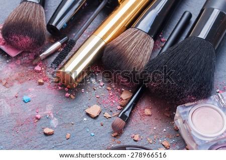 set of  make up brushes, lipsticks and  maskara on black background - stock photo