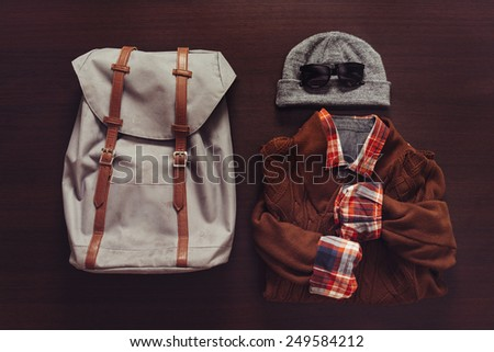 Set of male clothing and backpack in hipster style on wooden background, top view - stock photo