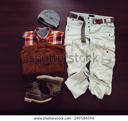 Set of male clothing in hipster style on wooden background, top view - stock photo