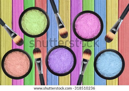 set of many eyeshadows and brushes on painted color wooden texture  - stock photo