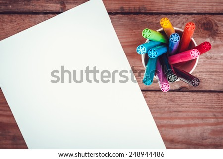 Set of markers in a paper cup and a piece of paper on old wooden table. Top view. concept - stock photo