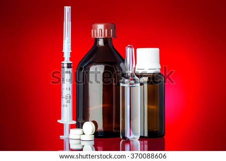 Set of medicines for health on glass with reflection on a red background. - stock photo