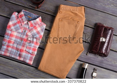 Set of men's clothing. Clothing and accessories on a wooden background. - stock photo
