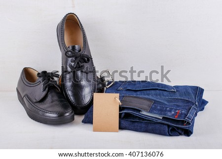 Set of men's clothing, shoes, jeans and a belt with blank tag on white wooden background