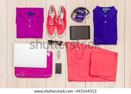 Set of men's clothing,tablet, smartphone, laptop and headphone on wooden background. T-shirt, polo shirt in bright colors and jeans. Top view - stock photo