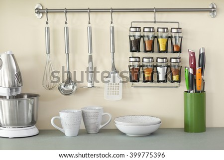 Set of metal kitchen utensils with spices hanging on the wall and mixer - stock photo