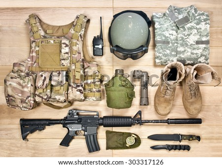 set of military equipment of the 21st century on a wooden background - stock photo