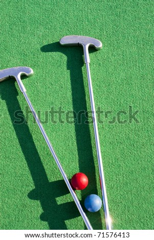 Set of mini golf clubs and color balls on green covering - stock photo