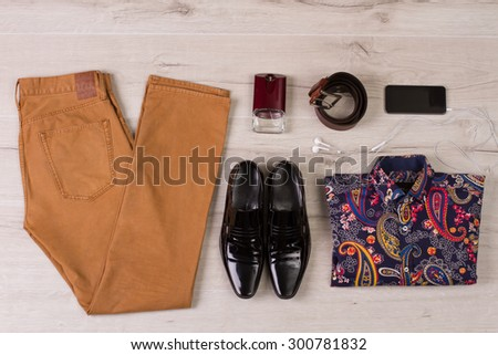 Set of modern men's clothing on a white wooden background. - stock photo