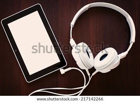 Set of modern white headphones attached by a cable to an MP3 player with a blank white screen visible to the viewer in a music and audio concept, on black - stock photo