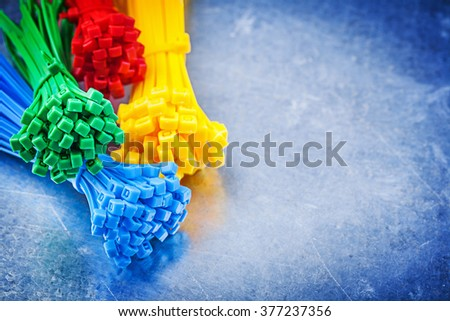 Set of multicolored plastic tying cables on scratched metallic background. - stock photo