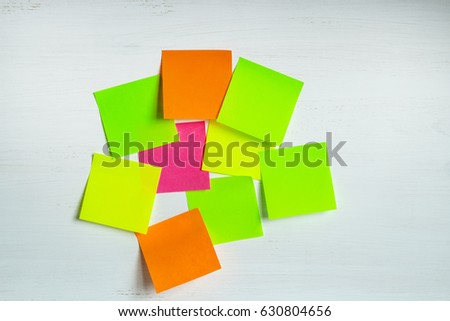 Set of multicolored stickers or sheets of paper on a white wooden background. Horizontal.