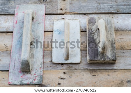 Set of old used trowels on a rough wooden surface - stock photo