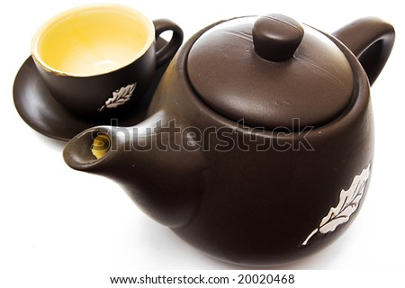 Set of one teapot and cup, closeup over white - stock photo