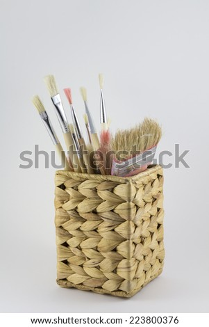 Set of paintbrushes in a wicker pot - stock photo