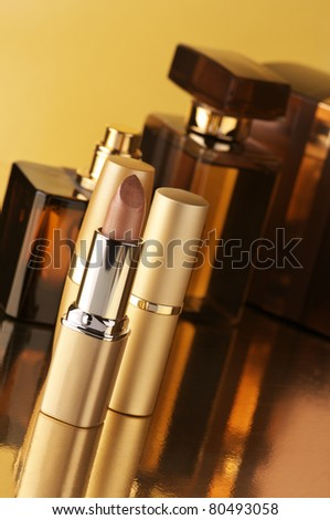 Set of perfumes and lipsticks on gold background.