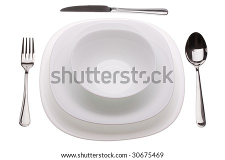 Set of plates with tablewares on white background
