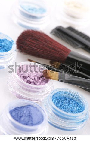 Set of powder eye shadows in jars and brushes close-up.