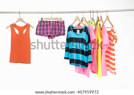 Set of rainbow many peignoir and t-shirt hanging on wooden hangers - stock photo