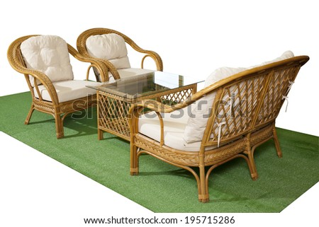 Set of rattan furniture for balcony and garden on artificial grass isolated on white background - stock photo