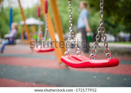 Set of red chain swings on modern kids playground - stock photo