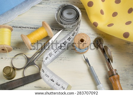 Set of reel of thread, centimeter, fabric, thimble and scissors, seam ripper and toothed wheel for sewing and needlework on the wooden board in Shabby Chic style. - stock photo