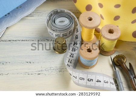 Set of reel of thread, centimeter, fabric, thimble, seam ripper and toothed wheel for sewing and needlework on the wooden board in Shabby Chic style. Still life photo with tools for handmade. - stock photo