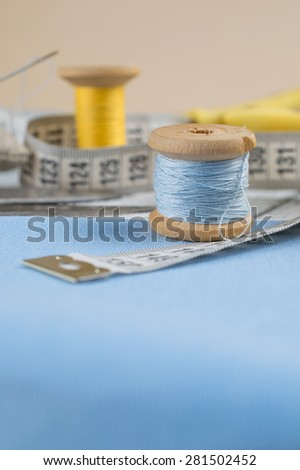 Set of reel of thread, scissors, centimeter, fabric and needle for sewing and needlework. Still life photo with tools for handmade. - stock photo