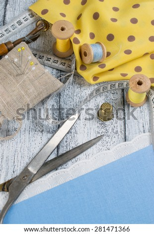Set of reel of thread, scissors, centimeter, toothed wheel, thimble, fabric, needle and pins for sewing and needlework in Shabby Chic style. Still life photo with tools for handmade. - stock photo
