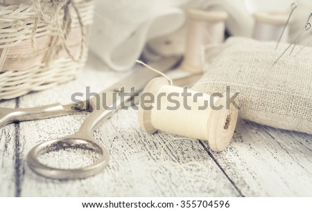 Set of reel of thread, scissors, needle and pins for sewing and needlework in Shabby Chic style. For this photo applied toning in retro style. - stock photo