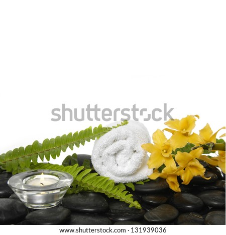 Set of roller towel with green fern and yellow orchid, candle on pebbles - stock photo