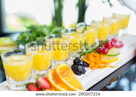 Set of several bright glasses with cold alcoholic cocktail with orange juice on a wooden table in a restaurant with ice and creative decoration of berries, fresh mint and orange slices. soft focus - stock photo