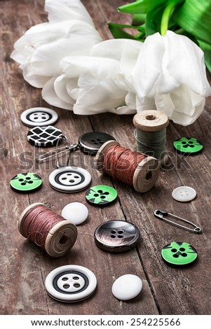 set of sewing accessories from threads and buttons on the background of white tulips - stock photo