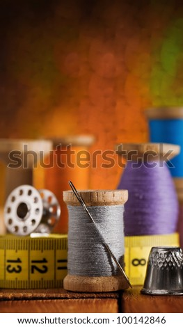set of sewing items on wooden table - stock photo