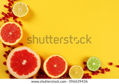 Set of sliced citrus fruit with pomegranate seeds on yellow background