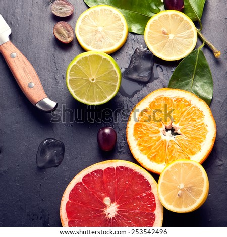 Set of sliced citrus fruits lemon, lime, orange, grapefruit with ice and vintage knife over stone black background. Top view. - stock photo
