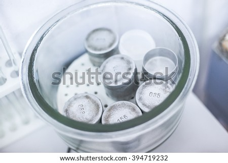 Set of small metal weights in glass case