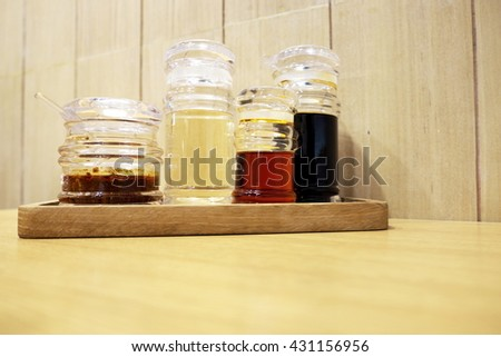 Set of soy sauce bottles on wooden plate, table and wall background. Focus on red-brown sauce.