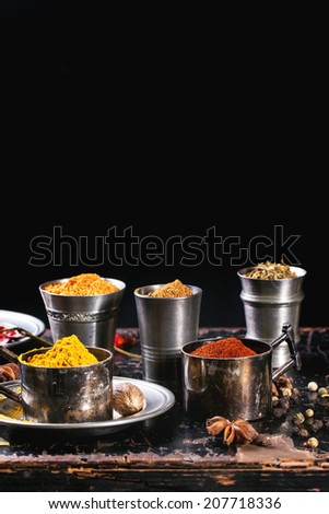 Set of spices pepper, turmeric, anise, coriander in vintage metal cups over old wooden table - stock photo