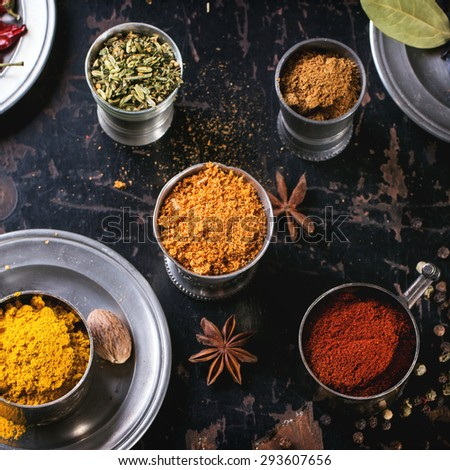 Set of spices pepper, turmeric, anise, coriander in vintage metal cups over old wooden table. Top view. Square image. - stock photo