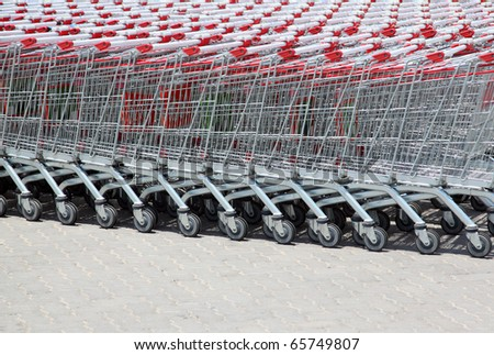 Set of stacked supermarket trolleys with red handle out of doors - stock photo