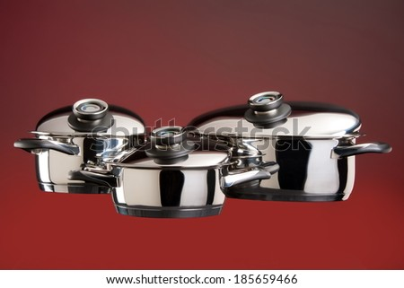 Set of stainless steel cookware on a red background - stock photo