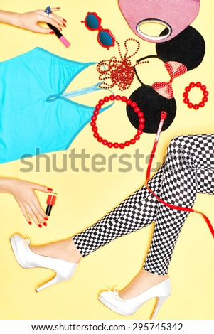 Set of stylish fashion clothes, womans sexy slim legs and girls hands. Vivid party accessories. Glamor top, leggings, trendy shoes for disco look. Unusual, provocative lady on yellow, copyspace.  - stock photo